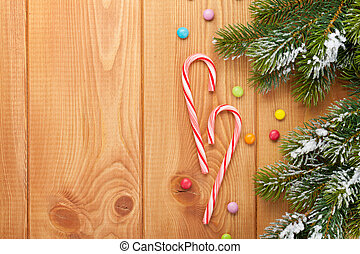 Christmas wooden background with snow fir tree and candies
