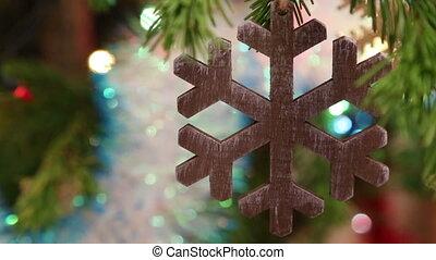 christmas wooden snowflake hanging on fir twig