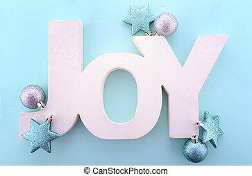 Christmas wooden word, Joy on blue background.