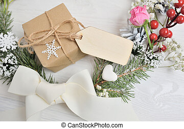 christmas wreath background with blank wooden tag for your text. Bow, christmas gift, pink rose and cones. Holiday composition