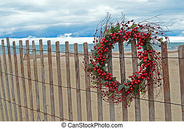 christmas wreath  - Berry holiday wreath on beach fence.