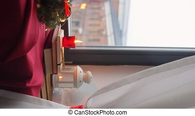 winter holidays and decorations concept - christmas fir wreath, books, candle and lantern on window sill at home, vertical view orientation