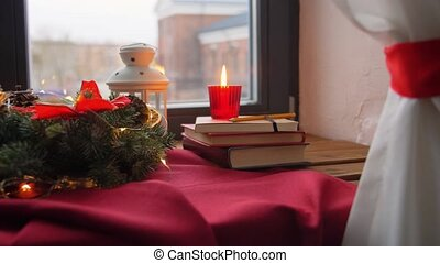 winter holidays, new year and decorations concept - christmas fir wreath, books, candle and lantern on window sill at home