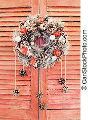 Christmas wreath hanging on wooden blinds