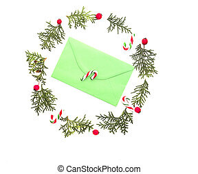 Christmas wreath made of thuja twigs, red wild rose fruits with green envelop and  candy cane in the middle. White background. Top view, flat lay.