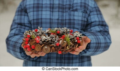 Christmas wreath of cones in the hands of a child - New...