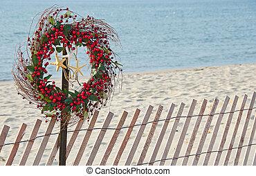 Christmas wreath on beach fence