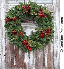Christmas wreath on a rustic wooden front door.