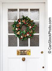 Christmas wreath hanging on door of a home