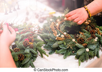 Christmas wreath weaving workshop. Woman hands decorating holiday wreath made of spruce branches, cones and various organic decorations on the table