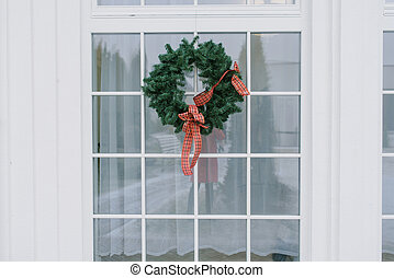 Christmas wreath with a red bow on a white window in a private house