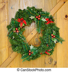 christmas wreath with decorations on wood door