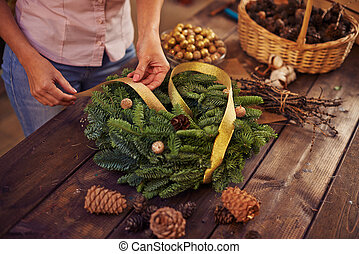 Christmas wreath - Woman decorating coniferous wreath