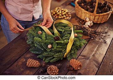 Christmas wreath - Woman decorating coniferous wreath