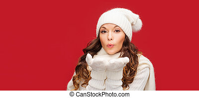 happy woman in winter clothes blowing on palms - christmas,...