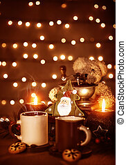 Festive still life on the table, beautiful glowing garland on the wall, two mugs with tea with homemade gingerbread, burning candle, Christmas decoration