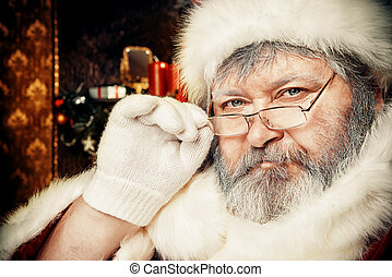 Portrait of smiling Santa Claus in a room decorated for Christmas.