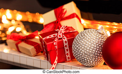 Chritmas balls and gift boxes on piano keyboard