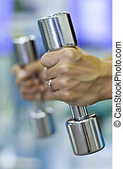 Chrome Dumbbells - A female fitness instructor holds a pair...