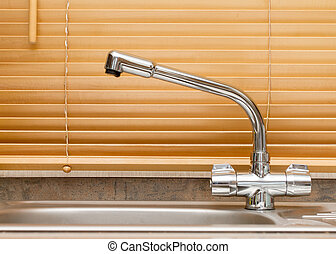 Chrome kitchen tap with venetian blind behind