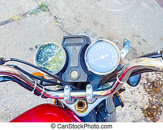 Closeup photo of chrome motorcycle handlebar with wires speedometer and tachometer