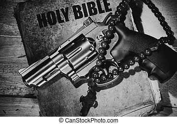 revolver and cross on an old bible on a wooden table