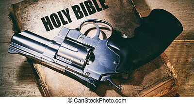 revolver on an old bible on a wooden table