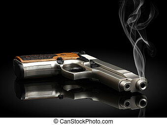 handgun on black background with smoke - Chromed handgun on...