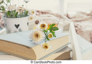 Chrysanthemum flowers lay on the book which is laying on the...