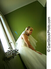 Beautiful girl in a wedding dress at a window with chrysanthemums