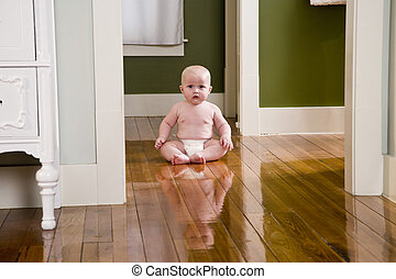 Chubby seven month old baby at home sitting on floor -...