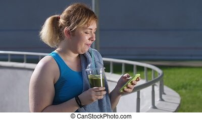 Chubby woman using phone and drinking smoothie - Close-up of...