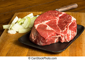 Raw cut of beef chuck roast and onions on a cutting board