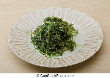 Chuka salad with sesame seeds on the wood background