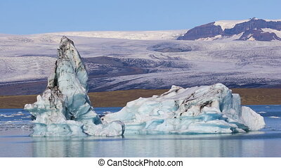 Chunk of ice floating in glacial lake Jokulsarlon, Iceland -...