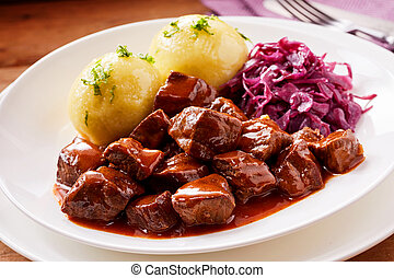 Chunky beef stew with savory sauce beside potato topped with...