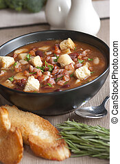 Delicious soup with chunks of meat, beans and croutons in a bowl