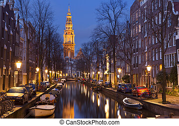 Church and a canal in Amsterdam at night - A church tower at...