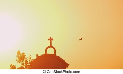 Church and flying bird against bright sunset shine