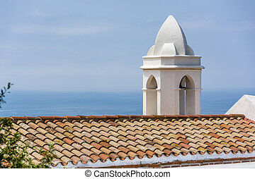 Church Bell tower against a blue mediterranean sea