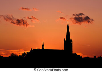Church building exterior in silhouette of sunrise or sunset with glowing sunlight