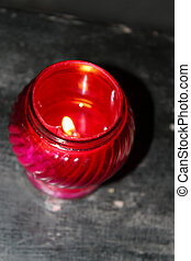 church candle burning in red candlestick