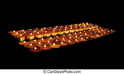 Church Candles In The Dark - Rows of candles burning in dark...