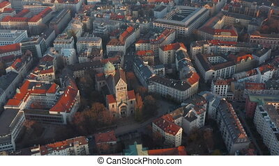 Church Cathedral Building in the middle of German Residential Neighbourhood in Munich, Bavaria, Scenic Aerial Slide right tilt down above red rooftops 4K