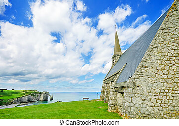 Church, Etretat village, beach, and Aval cliff. Normandy, France.