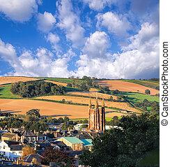 Church in Totnes against countryside in England, UK