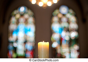 church interior with candle and stained glass windows