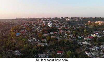 Church of Saint George and Kamianets Podilskyi Castle, prominent landmarks in this Ukrainian town, from a retreating, aerial perspective.