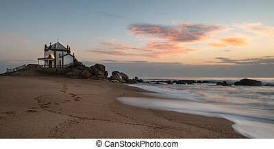 The famous and Picturesque church of Senhor da pedra south of Porto in Portugal in the Atlantic ocean during sunset.