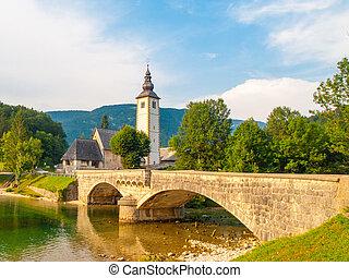 Church of St John the Baptist and old stone bridge at Lake Bohinj in alpine village Ribicev Laz, Julian Alps, Slovenia